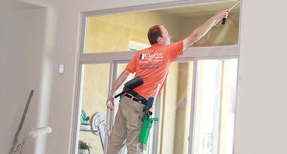 window cleaning technician cleaning an upper window from a step ladder