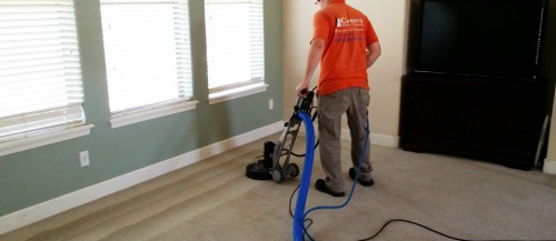 worker with machine cleaning carpet